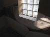 La bordure de la fenêtre en blocs de verre dans le vestibule refaite en plâtre avec un nouveau coin en acier